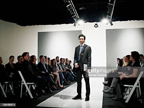Cool geek standing on catwalk at fashion show