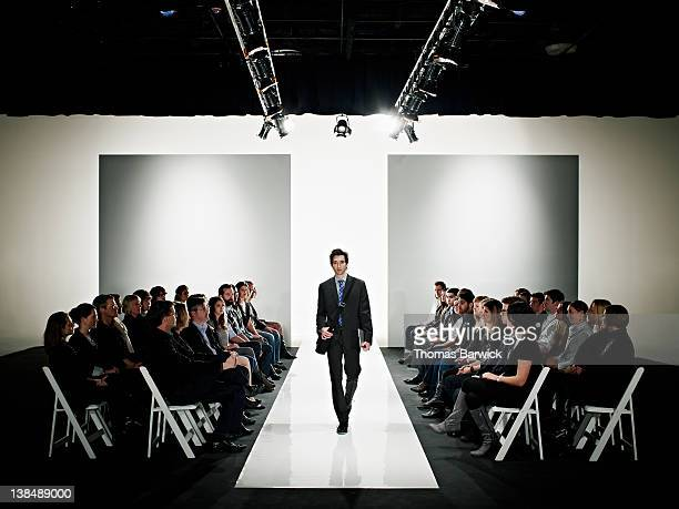 Cool geek walking down catwalk at fashion show