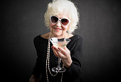Cool grandma with sun glasses on havinga a drink