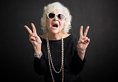Cool grandmother with sun glasses  showing peace sign