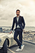 Cool guy with sports car on road, portrait