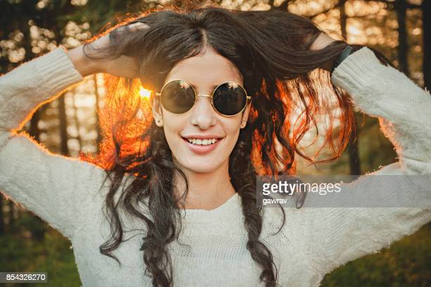 Cool, happy beautiful young woman holding her hair.