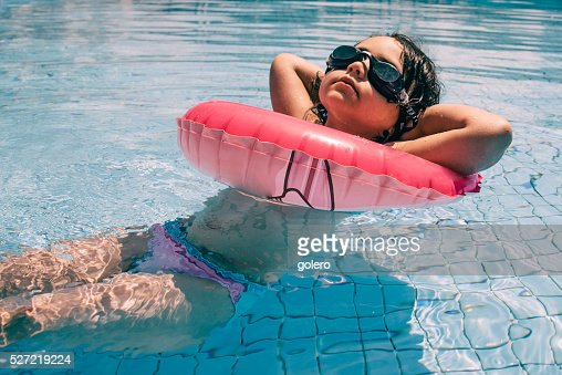 cool little girl in bikini and swim glasses in pool