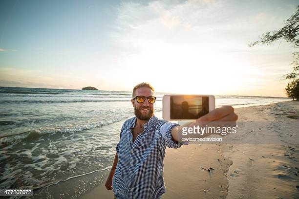 Cool man taking selfie on beach at sunset