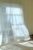 Cool ocean breeze blowing through the bedroom window as morning light lights the sheer curtains.