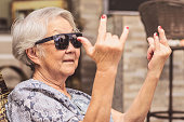 Cool old lady, wearing sunglasses doing the rock sign.