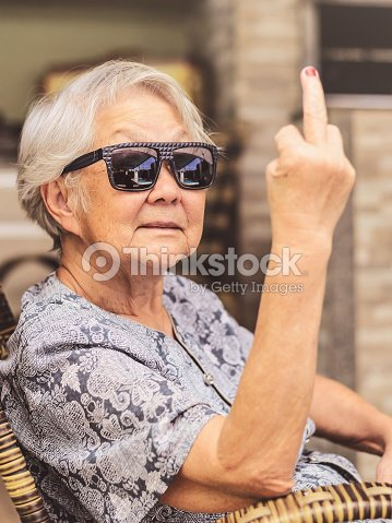 Cool old lady, wearing sunglasses, expressing herself showing the middle finger. : Stock Photo