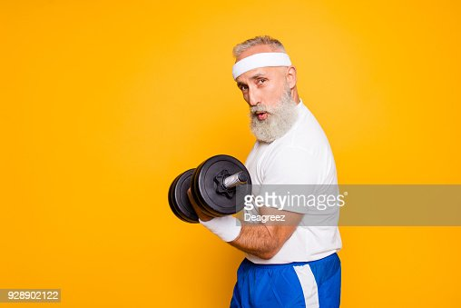 Cool playful flirty naughty strong grandpa with confident grimace exercising holding equipment up, lifts it with strength and power. Body care, fitness, body building, hobby, weight loss lifestyle : Foto de stock