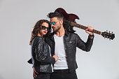 cool punk man holding guitar on shoulder and  embracing his woman ; rock and roll couple on grey background