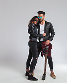cool rock and roll couple standing embraced, full body picture on grey studio background