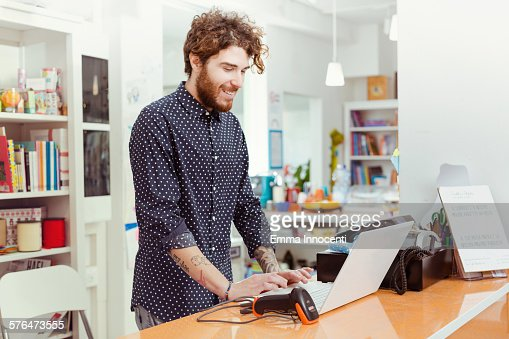 cool shop owner using laptop cashier stock photo getty images