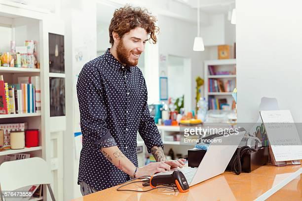 cool shop owner using laptop cashier