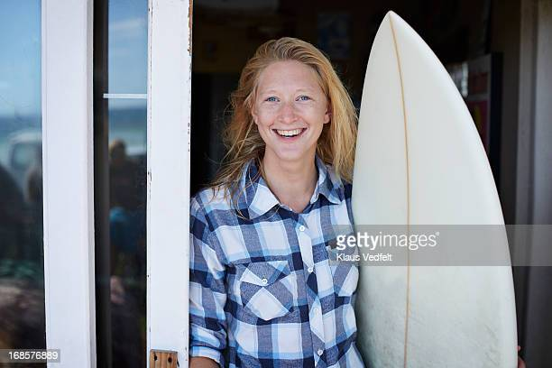 Cool surf girl laughing with surfboard