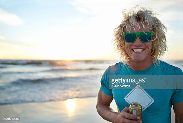 Cool surfer guy laughing to camera, at the beach