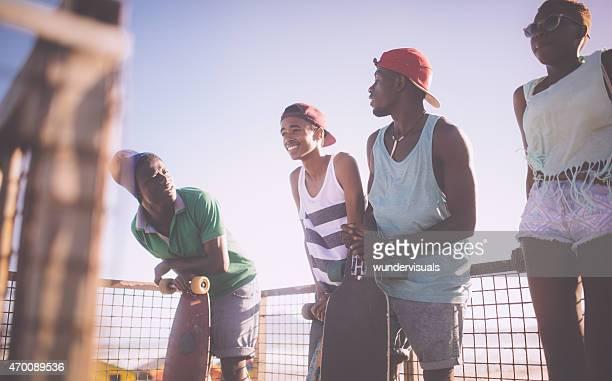 Fresco longboarder adolescente sorridente e a conversar com os seus amigos