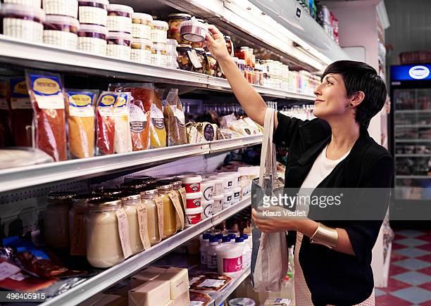 Cool woman picking goods at supermarket