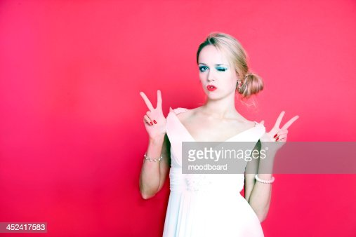 Cool woman wearing white dress on red background : Foto stock