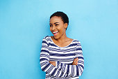 Portrait of cool young black woman laughing against blue wall