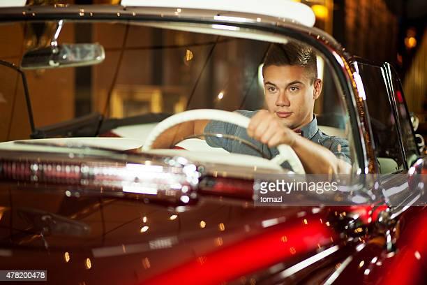 Cool junger Fahrer eines alten Auto