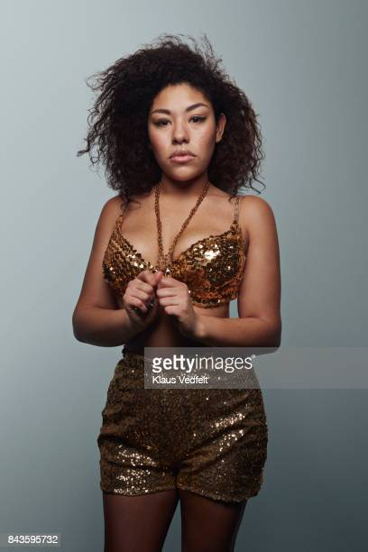 Cool young woman wearing gold party clothes, looking in camera