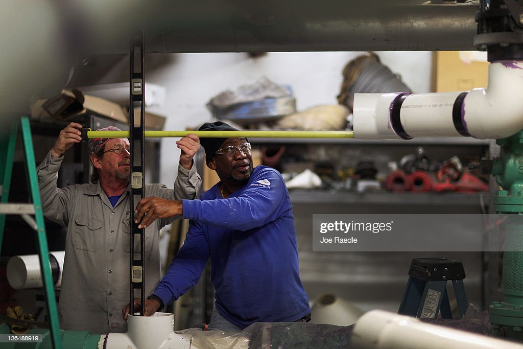 Cool-Breeze Air Conditioning supervisor Mike Trent (L) works with recently hired, Mike Turner on installing an air conditioner in a hotel on January 6, 2012 in Miami Beach, Florida. The most recent jobs report for the month of December indicated that 200,000 new jobs were created in the month, and the unemployment rate dropped to 8.5 percent.