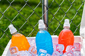A red and white ice chest full of ice and several plastic bottles of colorful ice cold sports drinks on a hot Summer day with a chain link fence in the background.