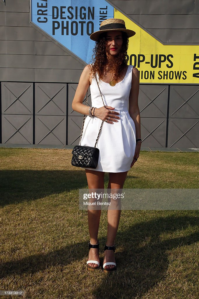 Coolhunter Clara de Nadal Trias wears a Top Shop hat, a Les Petites dress, a Chanel bag, BCBG shoes and vintage pendant made in gold from 1900's at the 080 Barcelona Fashion Week Spring/Summer 2014 on July 11, 2013 in Barcelona, Spain.