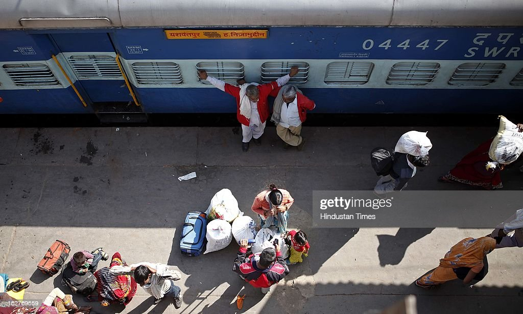 Coolies waiting for customers on platform at Nizamuddin railway station on February 26, 2013 in New Delhi, India. Indian Railway Minister Pawan Kumar Bansal presented his maiden Railway budget for the next fiscal year in the parliament.