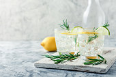 Cold lemonade or alcoholic cocktail with lemon, rosemary and ice in glass glasses on a light background
