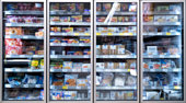 out of focus cooling shelves freezer in supermarket with different products