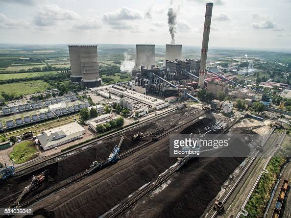 Cooling towers stand as conveyors transport brown coal at the Visonta open cast lignite mine operated by Matrai Eromu Zrt in Visonta Hungary on...