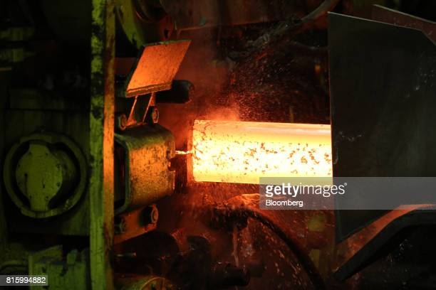 Cooling water sprays around a red hot steel slab as it passes through the rolling mill at the Oskol Elektrometallurgical Plant steel mill operated by...