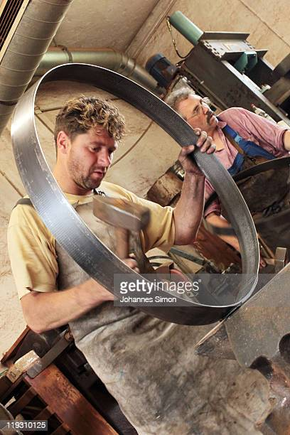 A cooper at the Schmid barrel factory assembles a wooden barrel destined to hold beer at the upcoming Oktoberfest on July 13 2011 in Munich Germany...