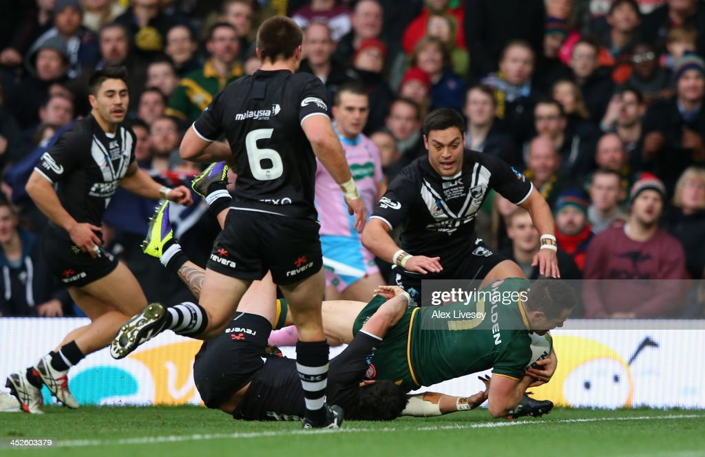 Cooper Cronk of Australia dives over the line to score a try during the Rugby League World Cup Final between New Zealand and Australia at Old...