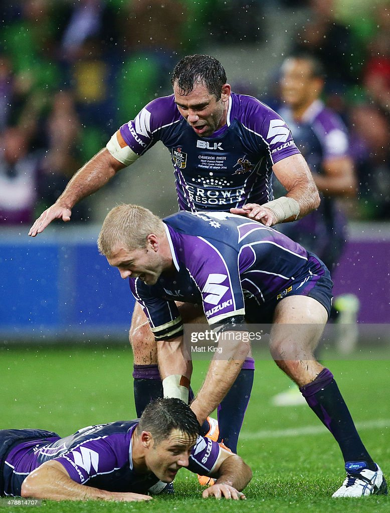 Cooper Cronk (bottom) of Storm celebrates with Ryan Hinchcliffe (middle) and Cameron Smith (top) after kicking the winning field goal during the round two NRL match between the Melbourne Storm and the Penrith Panthers at AAMI Park on March 15, 2014 in Melbourne, Australia.