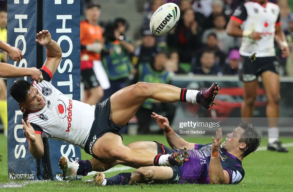 Cooper Cronk of the Melbourne Storm and Roger Tuivasa-Sheck of the Warriors compete for the ball during the round eight NRL match between the Melbourne Storm and the New Zealand Warriors at AAMI Park on April 25, 2017 in Melbourne, Australia.