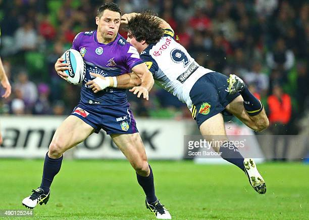 Cooper Cronk of the Melbourne Storm bests the tackle of a diving Jake Granville of the Cowboys during the NRL Second Preliminary Final match between...
