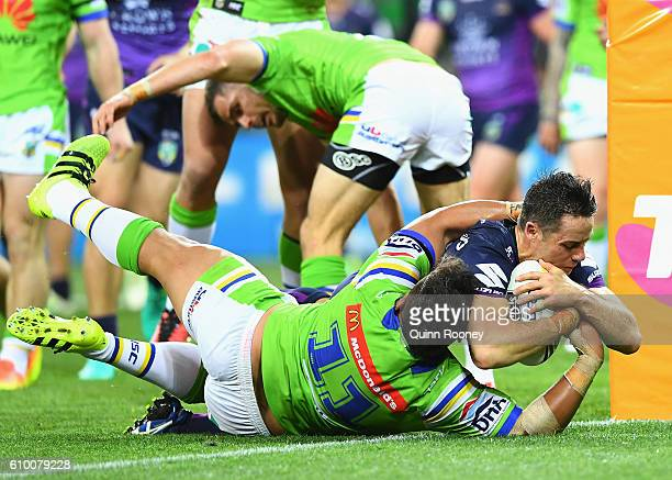 Cooper Cronk of the Storm breaks through a tackle by Josh Papalii of the Raiders to score a try during the NRL Preliminary Final match between the...