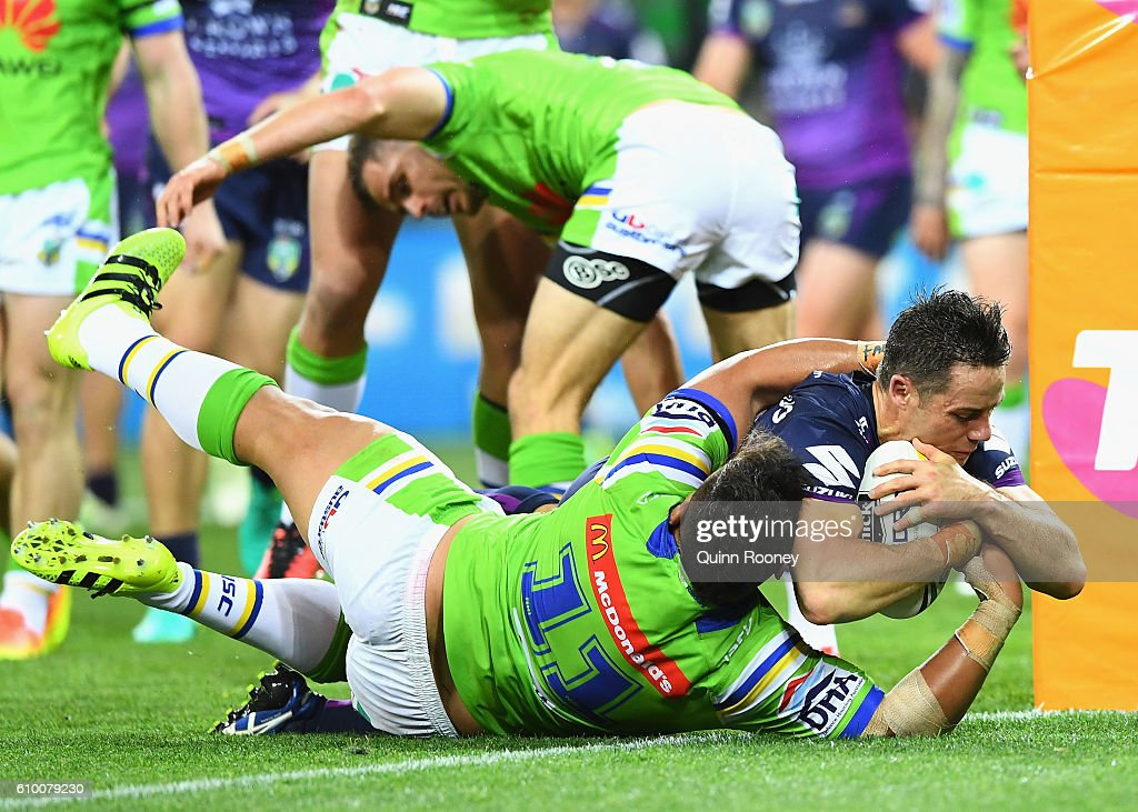 Cooper Cronk of the Storm breaks through a tackle by Josh Papalii of the Raiders to score a try during the NRL Preliminary Final match between the Melbourne Storm and the Canberra Raiders at AAMI Park on September 24, 2016 in Melbourne, Australia.
