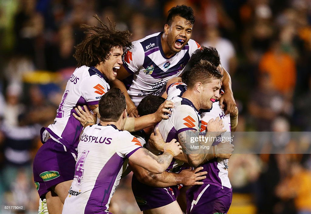 Cooper Cronk of the Storm (obscured) celebrates with team mates after kicking a field goal to win the match in golden point extra time during the round seven NRL match between the Wests Tigers and the Melbourne Storm at Leichhardt Oval on April 17, 2016 in Sydney, Australia.