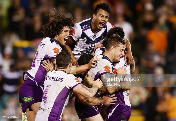 Cooper Cronk of the Storm celebrates with team mates after kicking a field goal to win the match in golden point extra time during the round seven...