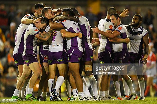Cooper Cronk of the Storm celebrates with team mates after kicking the winning field goal in extra time during the round seven NRL match between the...