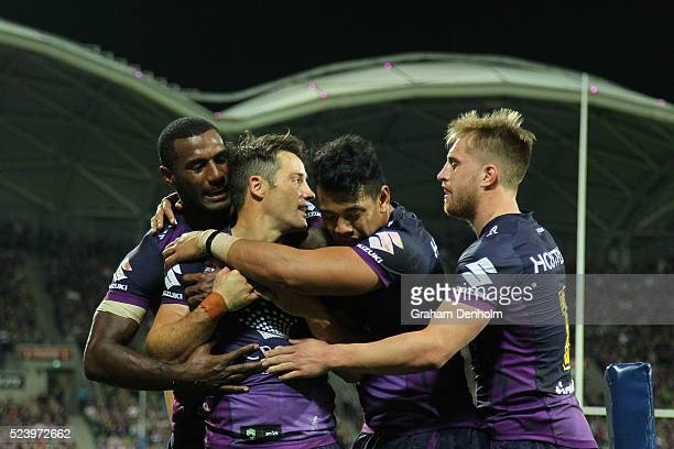 Cooper Cronk of the Storm celebrates with teammates after scoring a try during the round eight NRL match between the Melbourne Storm and the New...