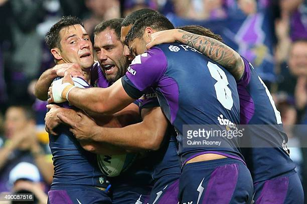 Cooper Cronk of the Storm is congratulated by team mates after scoring a try during the NRL Second Preliminary Final match between the Melbourne...