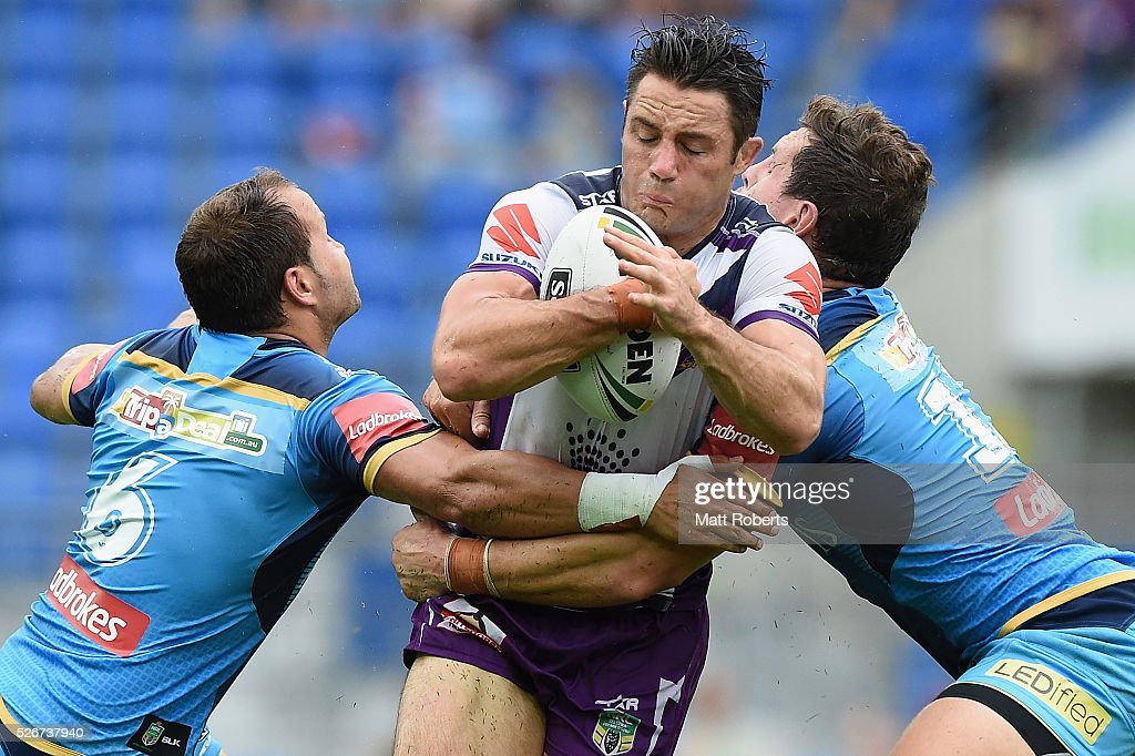 Cooper Cronk of the Storm is tackled by Greg Bird and Tyrone Roberts of the Titans during the round nine NRL match between the Gold Coast Titans and the Melbourne Storm on May 1, 2016 in Gold Coast, Australia.
