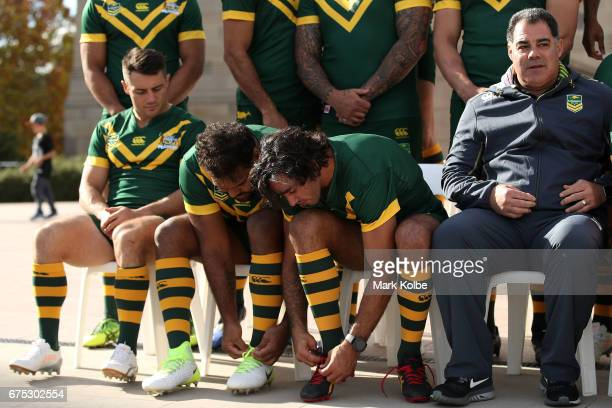 Cooper Cronk watches on as Sam Thaiday and Johnathan Thurston tie their laces as they prepare for a team photo during an Australian Kangaroos media...