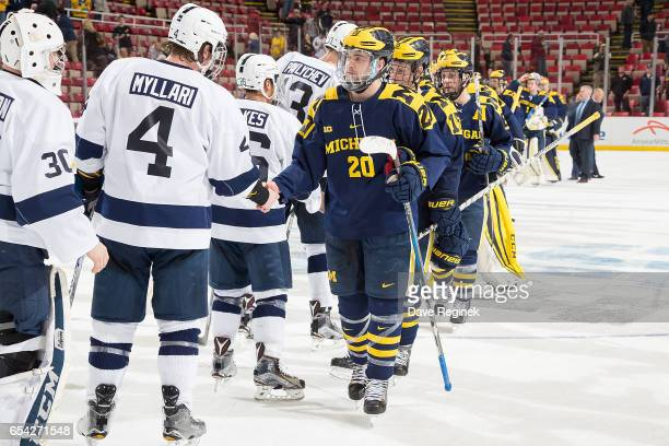 Cooper Marody of the Michigan Wolverines shakes hands at center ice with Kris Myllari of the Penn State Nittany Lions after game two of the Big Ten...