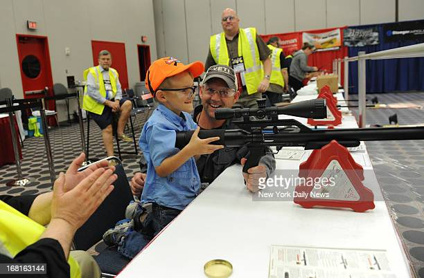 Cooper Mattison gets a pointer from his beaming dad Trent as he shoots an airsoft gun during kid's day at the NRA convention in Houston Texas