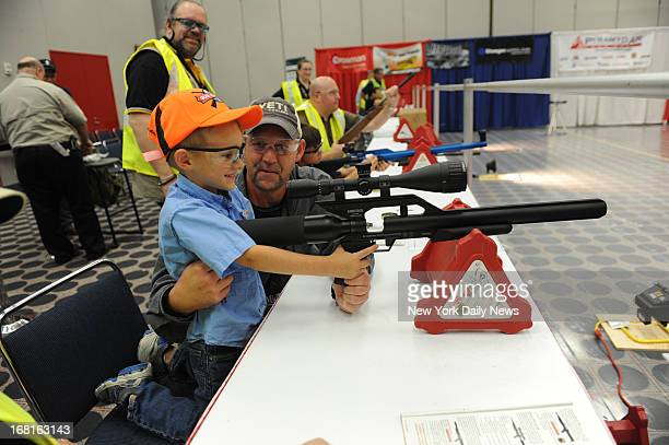 Cooper Mattison gets encouragement from dad Trent as he shoots an airsoft gun during kid's day at the NRA convention in Houston Texas