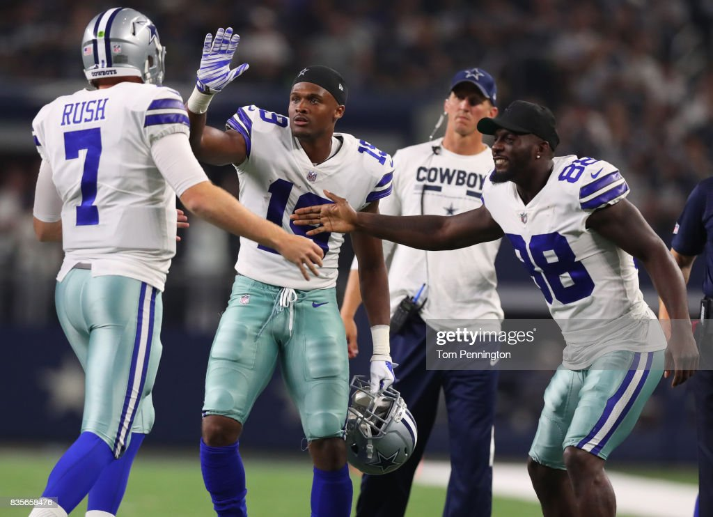 Cooper Rush #7 of the Dallas Cowboys is greeted on the sidelines by Brice Butler #19 of the Dallas Cowboys and Dez Bryant #88 of the Dallas Cowboys after throwing a touchdown pass in the second half of a preseason game at AT&T Stadium on August 19, 2017 in Arlington, Texas.
